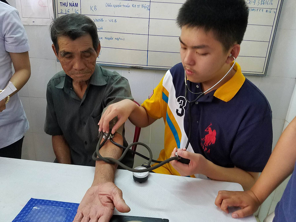 Cuong checking the blood pressure of an older patient at the Hue mobile clinic.