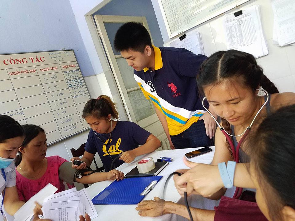 Cuong Luu checking Emira and Tori taking blood pressure